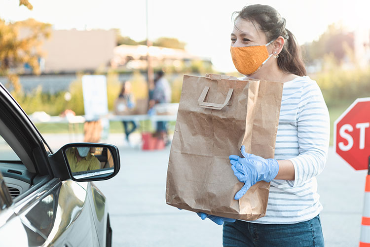 Finding joy in helping others. A woman hands a bag to a driver in a drive-through food drive.