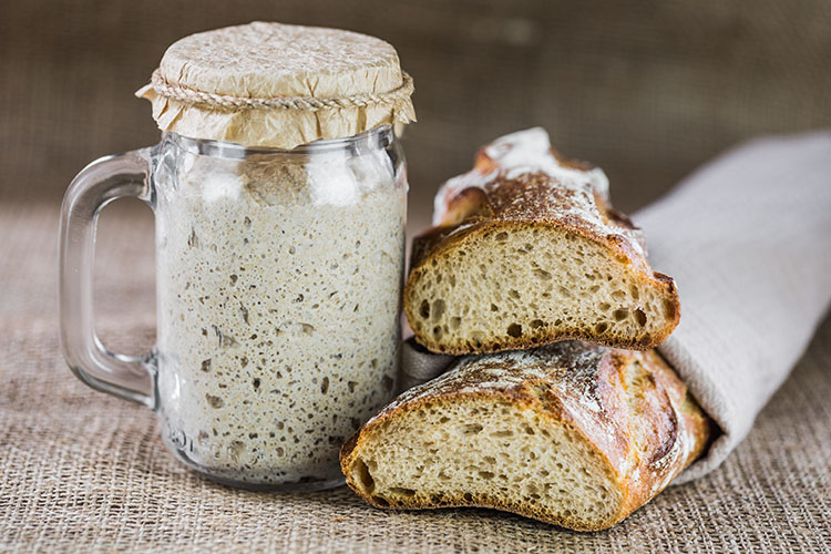 Finding joy in baking – A sourdough starter and a loaf of sourdough bread on the counter.